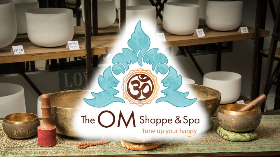 The Om Shoppe logo over a shelf full of frosted singing bowls